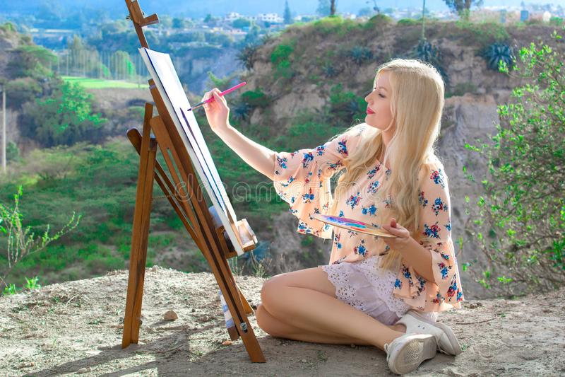 Beautiful young woman artist paints a landscape in nature. Drawing on the easel with colorful paints in the open air. Painting in nature, plein air royalty free stock images