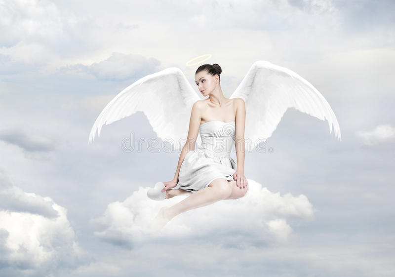 Beautiful young woman as angel sitting on a cloud royalty free stock image