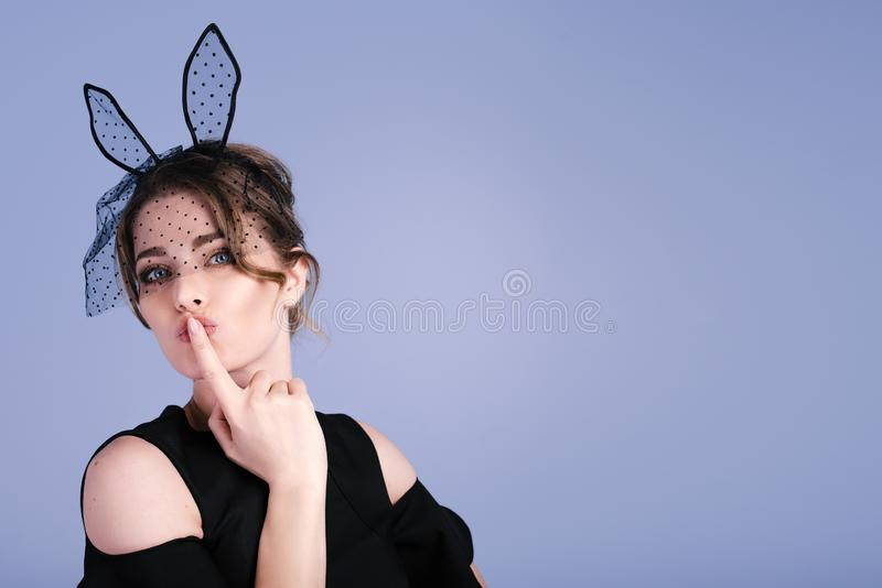 Beautiful young woman as easter bunny with rabbit ears on blue background stock photos