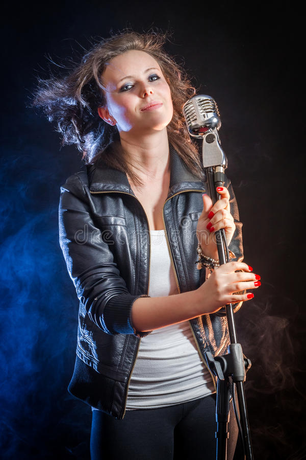 Beautiful young woman as a singer stock images
