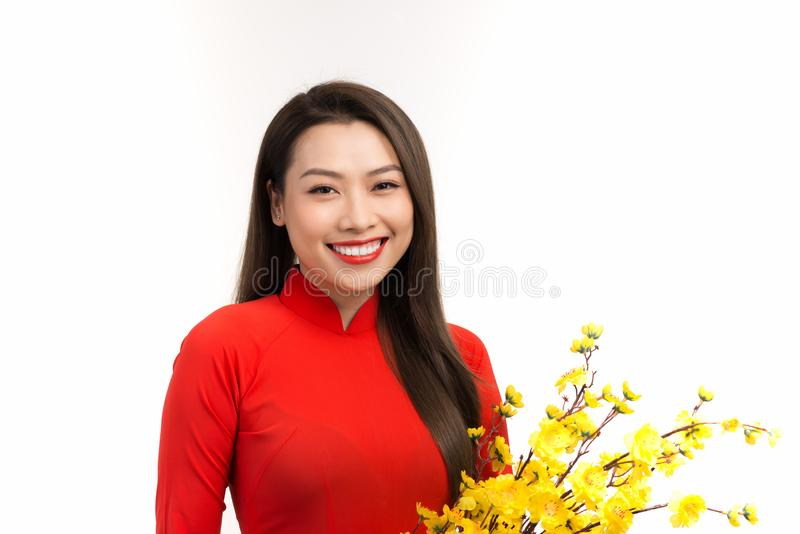 Beautiful young woman in asian outfit ao dai, holding apricot blossoms, smiling royalty free stock photo