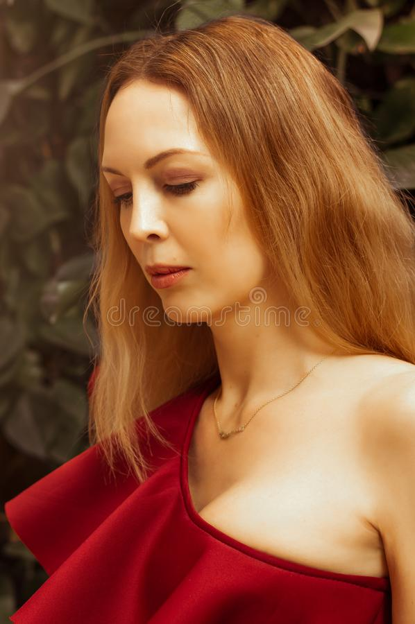 A beautiful young woman in an asymmetrical red-burgundy cocktail dress on one shoulder sits in a restaurant and happily smiles royalty free stock photos