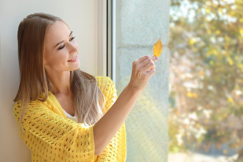 Beautiful young woman with autumn leaf near window at home stock photos