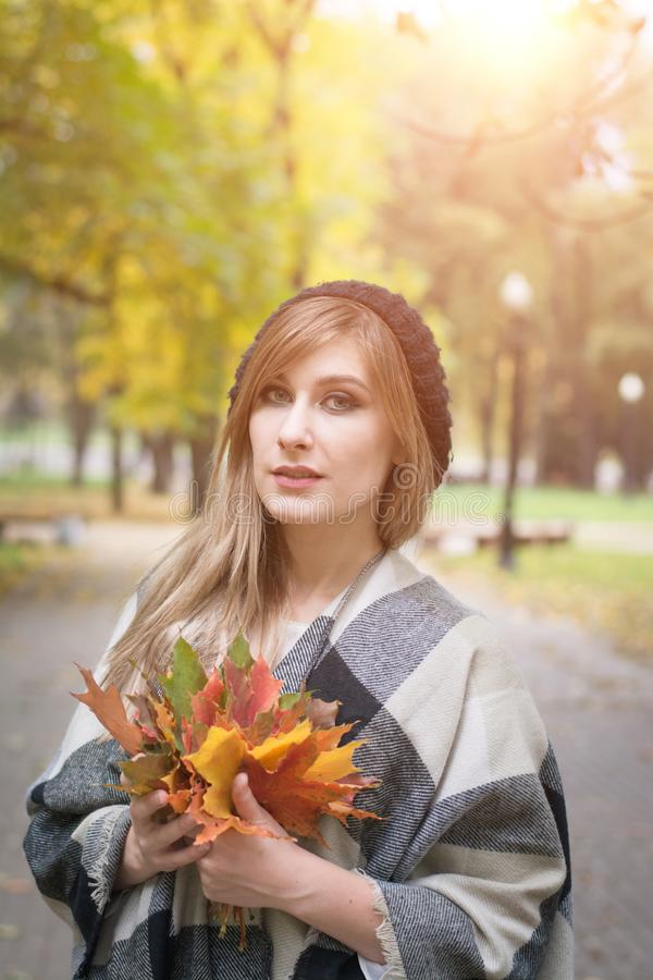 Beautiful young woman with autumn leaves royalty free stock photography