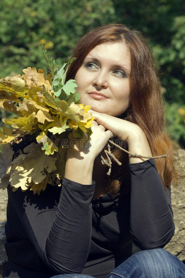 Beautiful young woman with autumn leaves in park royalty free stock images