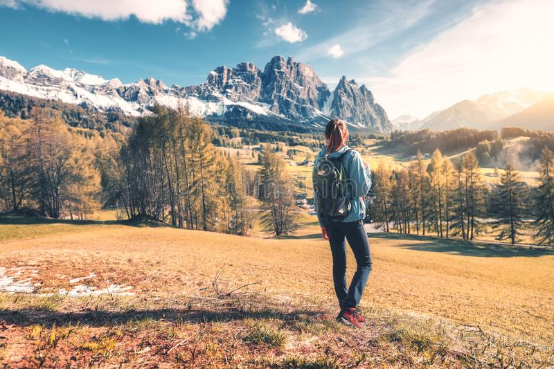 Beautiful young woman with backpack is standing on the hill. Against mountains at sunset in autumn. Landscape with sporty girl, rocks with snowy peaks, meadow royalty free stock photo