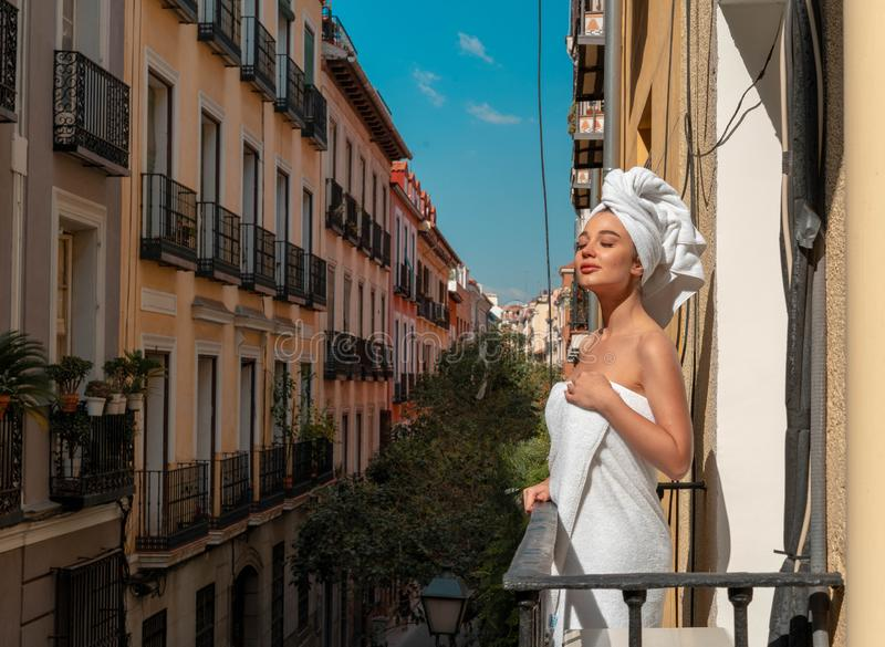 Beautiful young woman in towel at balcony in European old town enjoying summer sun and morning stock photo