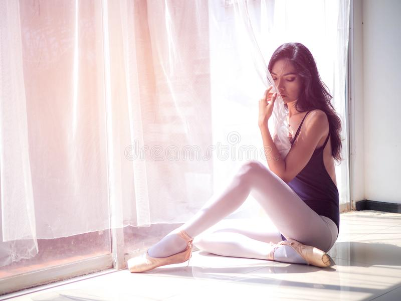 Beautiful young woman ballet dancer sitting on the floor.  royalty free stock photo