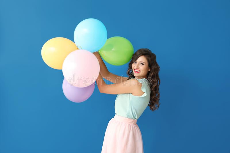 Beautiful young woman with balloons on color background stock photo