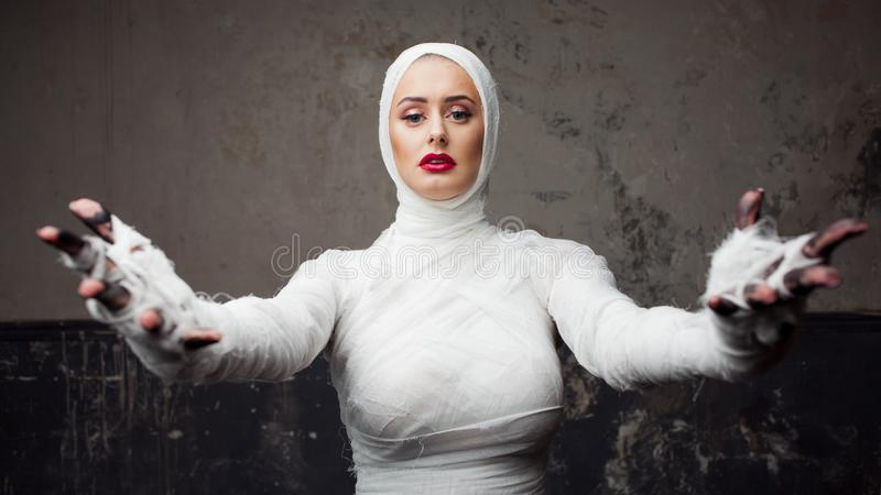 Beautiful young woman in bandages. Girl in a mummy costume, Pulling hand. Halloween or plastic surgery concept stock image