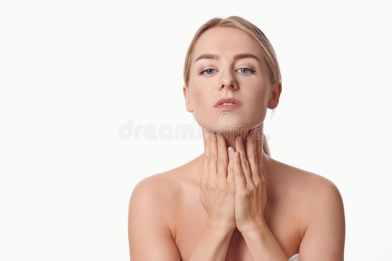 Beautiful young woman with bare shoulders massaging her throat royalty free stock photography