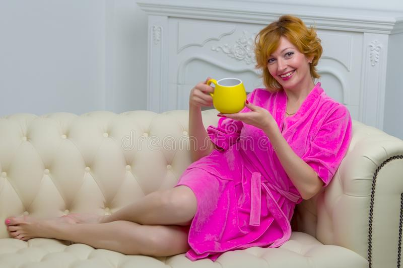 Beautiful young woman in a bathrobe relaxes on a sofa by the fir stock image