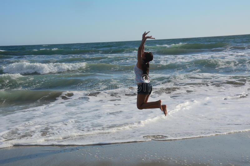 Beautiful young woman on the beach jumping for joy royalty free stock images
