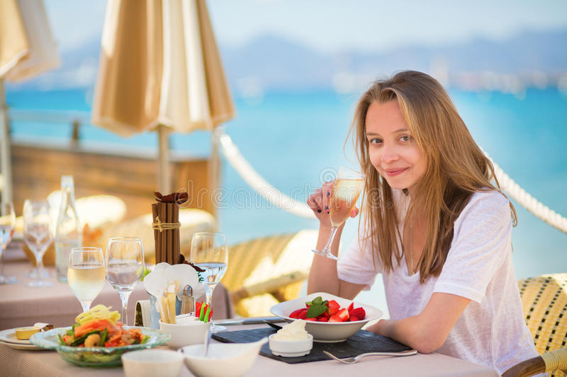 Beautiful young woman in a beach restaurant. Beautiful young woman drinking champagne in a beach restaurant royalty free stock photo