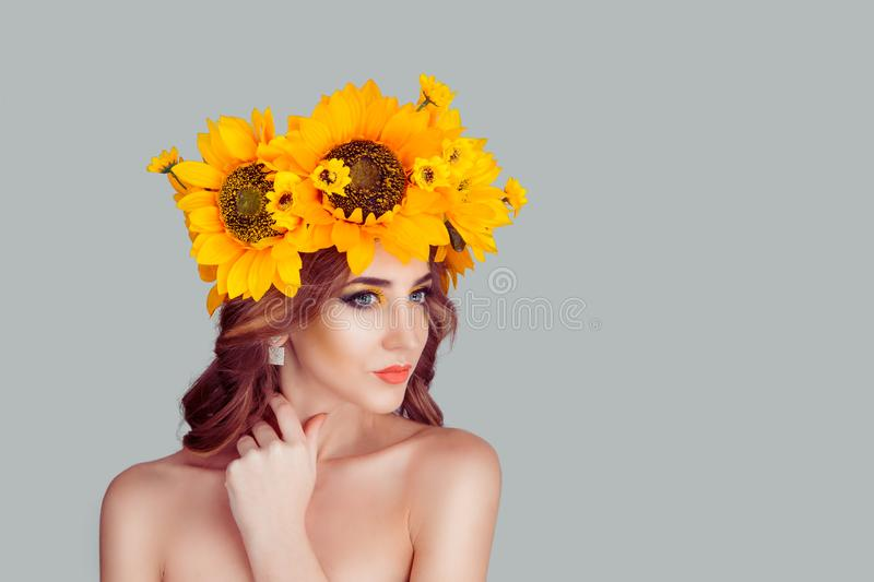 Woman with wreath headband of sunflower yellow flowers painting on face. Beautiful young woman beauty, fashion portrait with wreath headband of sunflower yellow stock photo