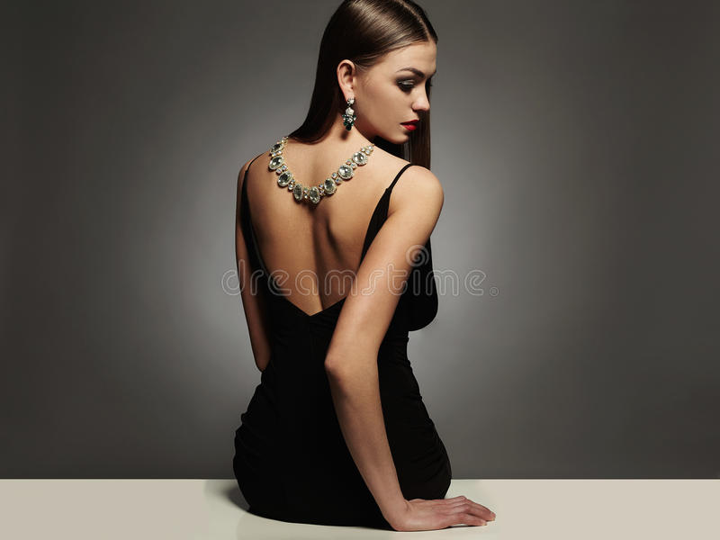Beautiful young woman.beauty sitting girl Girl with a necklace on her back. Beautiful young woman in a black dress.luxury.beauty brunette sitting girl Girl with stock image