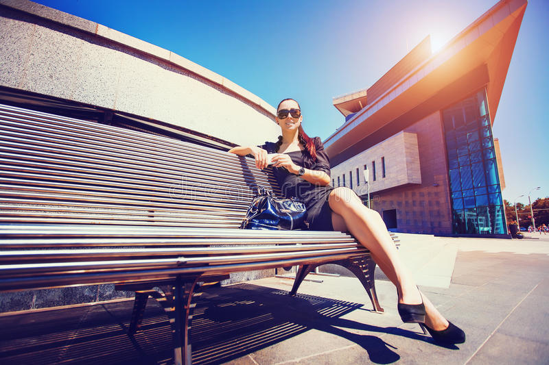 Beautiful young woman on the bench stock images