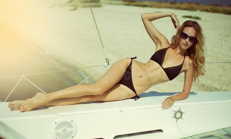 Beautiful young woman in a bikini relaxes and sunbathes aboard a white sea yacht royalty free stock image