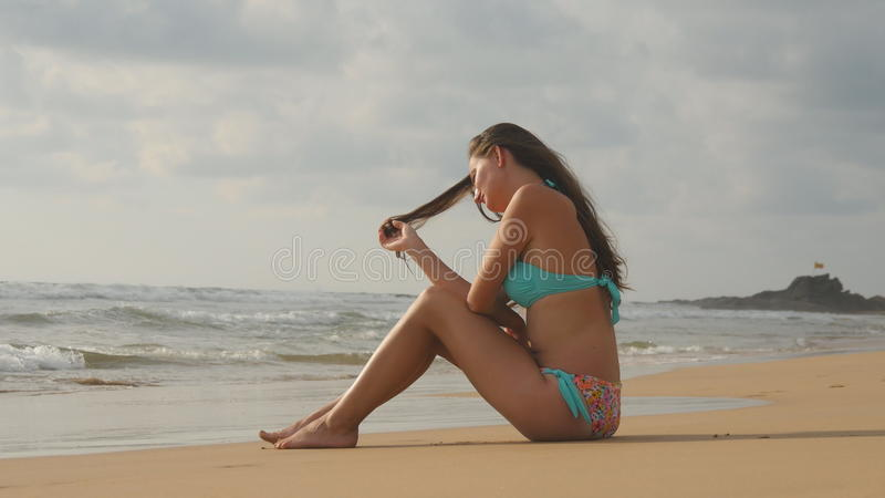 Beautiful young woman in bikini sitting on golden sand on sea beach. Tanned girl relaxing on perfect paradise shore royalty free stock photography