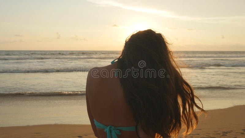 Beautiful young woman in bikini standing near the sea on sunset. Attractive girl with long hair posing on the ocean royalty free stock image