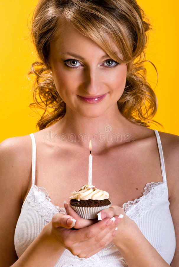 Beautiful young woman with birthday cake. Over yellow background royalty free stock image