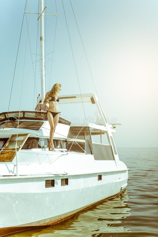Beautiful young woman in a bikini relaxes with binoculars in hands and sunbathes aboard a white sea yacht stock photography