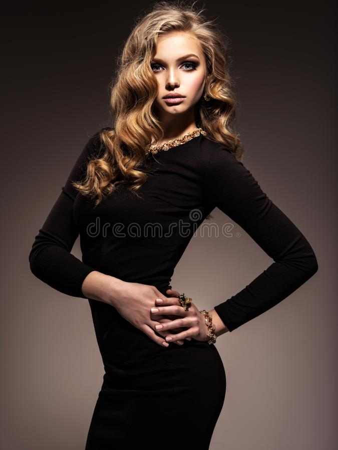 Beautiful woman in black bodycon dress with long curly hair stock photography