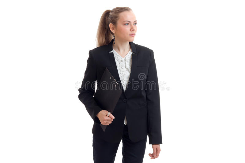 A beautiful young woman in a black business suit looks away and keeps the Tablet stock images