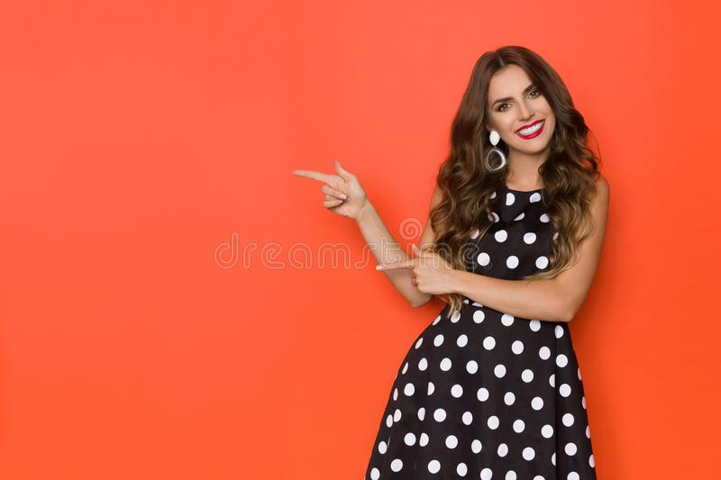 Beautiful Young Woman Is Black Coctail Dress In Polka Dots Is Pointing At Orange Copy Space And Smiling royalty free stock photography
