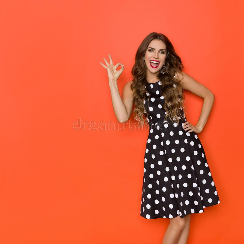 Beautiful Young Woman Is Black Coctail Dress In Polka Dots Is Showing Ok Hand Sing And Laughing stock photo