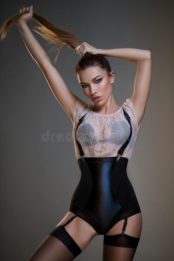 Beautiful young woman in black corset, white blouse and suspenders. Posing at camera against dark grey background royalty free stock images