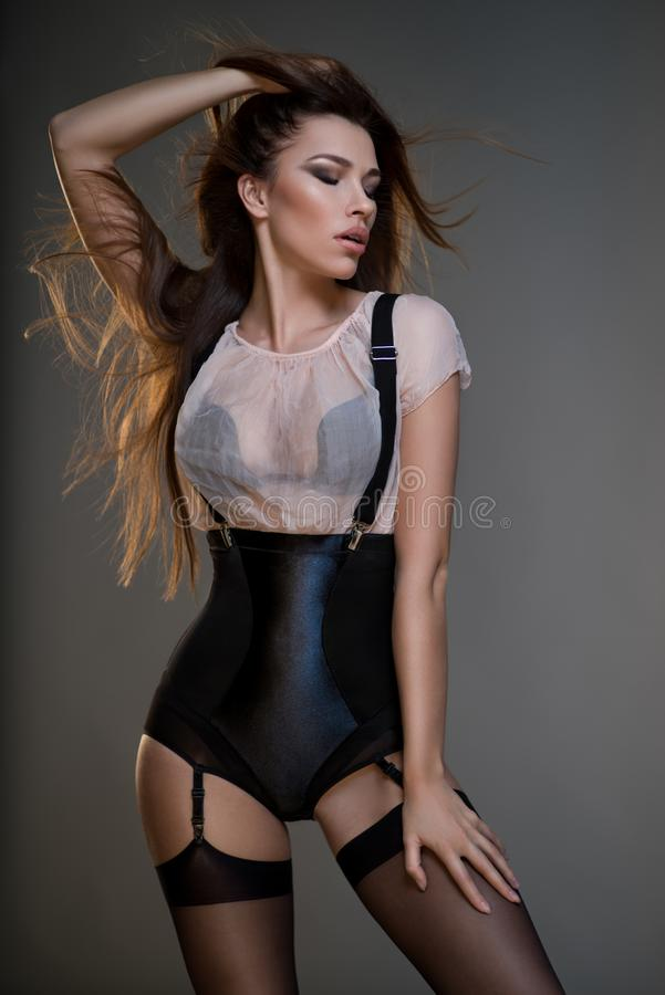 Beautiful young woman in black corset, white blouse and suspenders. Posing at camera against dark grey background stock photography