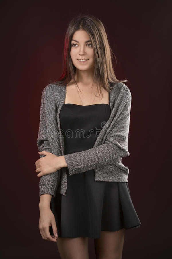Beautiful young woman in black dress. Dark red Background. stock photography