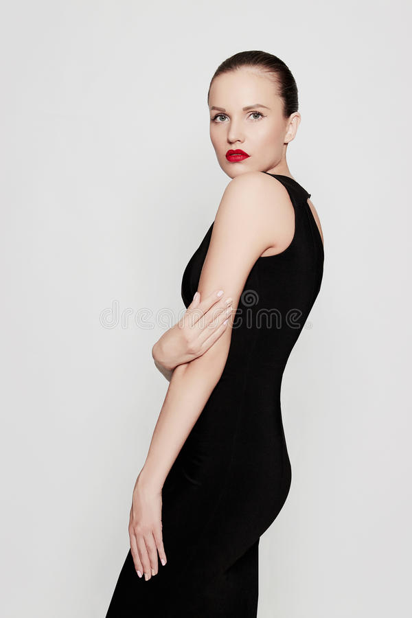 Beautiful young woman in a black dress stock image
