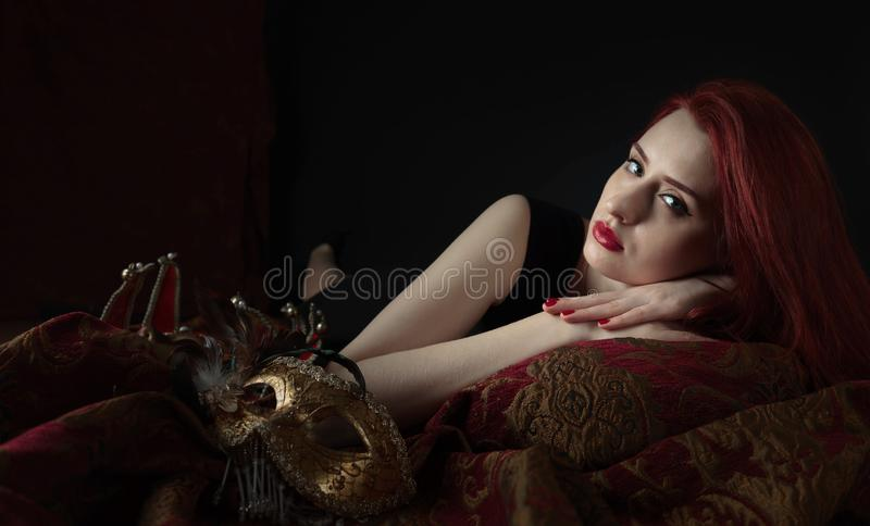 Beautiful young woman in black dress with carnival mask. royalty free stock image