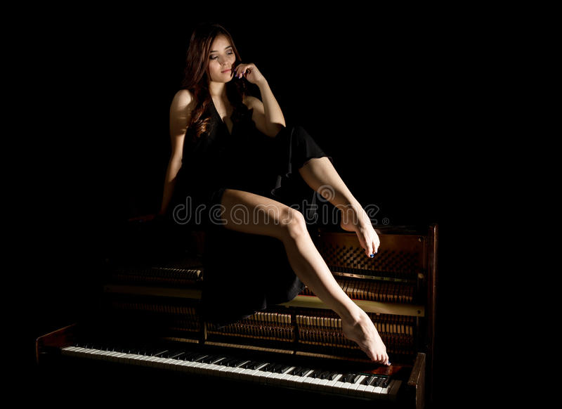 Beautiful young woman in a black dress with an open back sitting on a old piano on a dark background.  royalty free stock photos