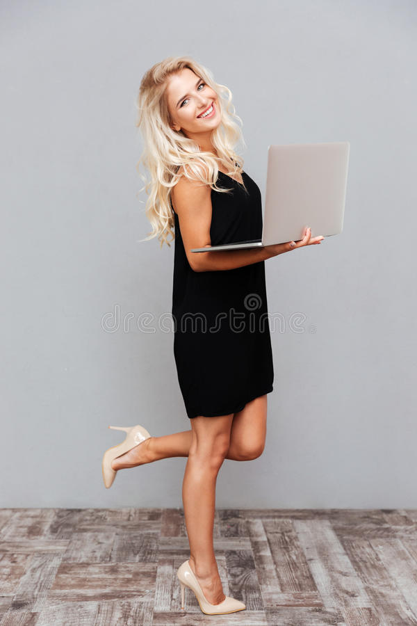 Beautiful young woman in black dress standing and holding laptop. Full length of happy beautiful young woman in black dress standing and holding laptop over gray stock image
