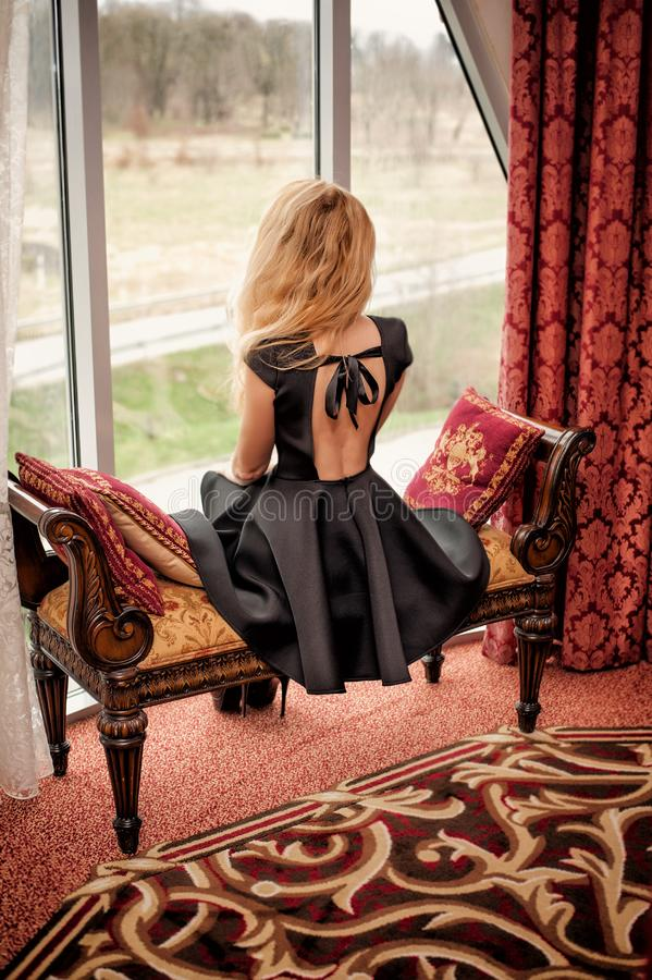 Beautiful young woman in black fashion dress with open back sitting stock photo