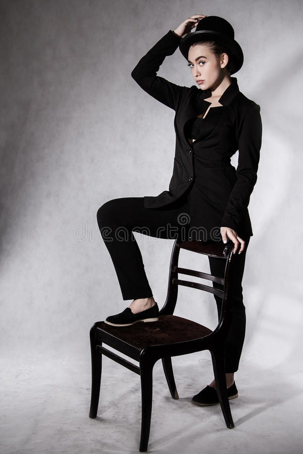 Beautiful young woman in a black hat and a black jacket stock photography