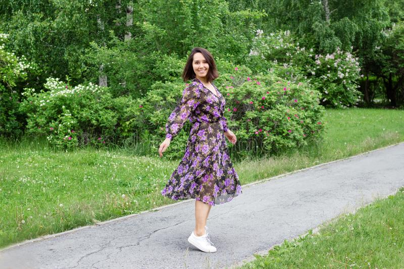 Beautiful young woman in black-purple dress is walking in a garden with blooming lilac bushes royalty free stock photos