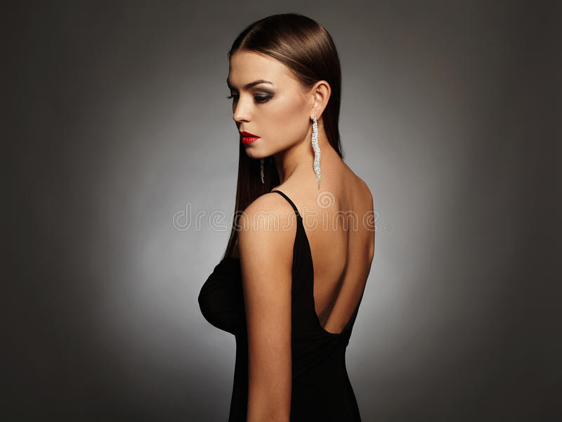 Beautiful young woman in a black dress posing in the studio,luxury.beauty brunette girl. Elegant fashion photo of glamor beautiful young woman in a black dress royalty free stock images