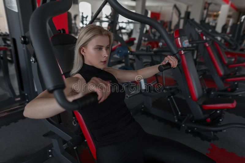 Beautiful young woman in black sportswear is engaged in sitting on the simulator in a fitness studio. royalty free stock photography