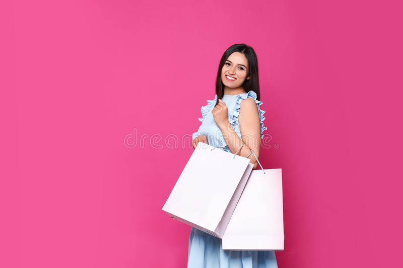 Beautiful young woman with blank paper bags against color background, space stock photos