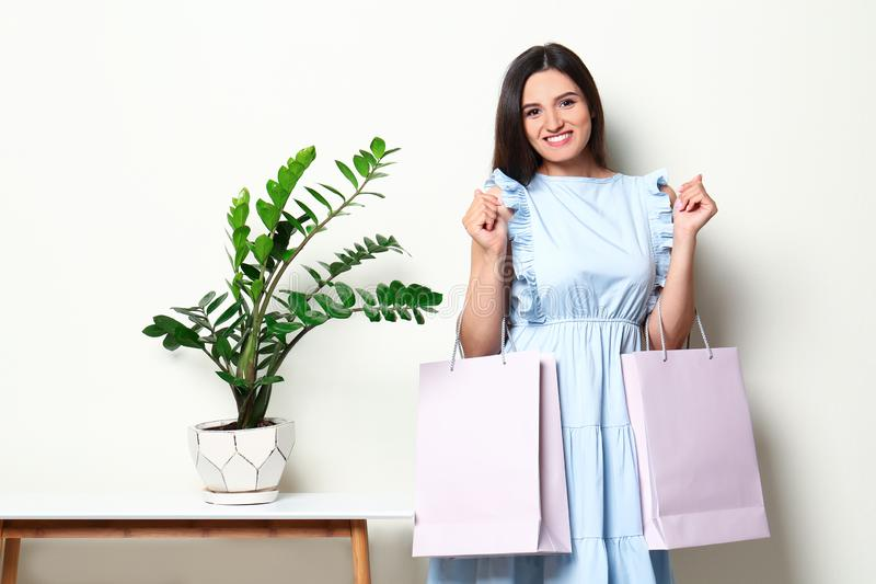Beautiful young woman with blank paper bags near white wall stock photography