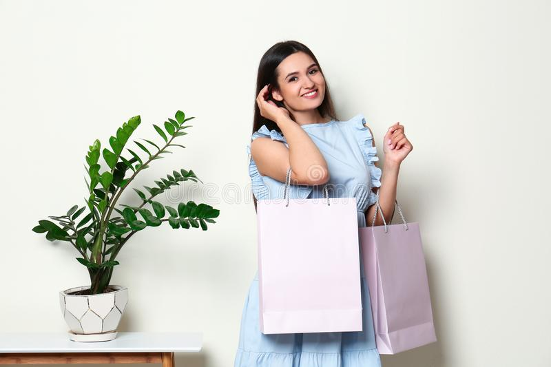 Beautiful young woman with blank paper bags near white wall, space for stock images