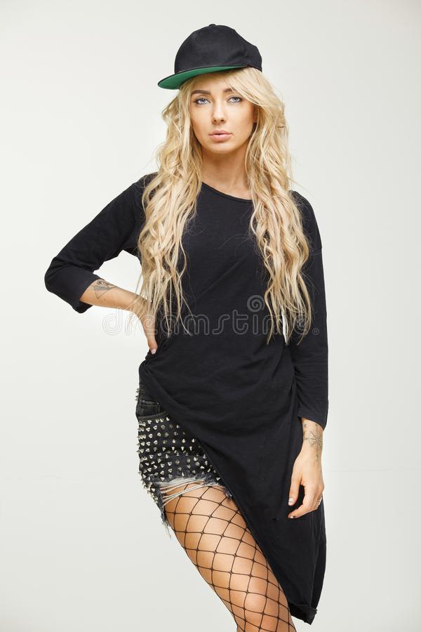 Beautiful young woman with blond long hair in stylish swag look on white isolated background. cap, long t-shirt, shorts. Mesh tights. fashion combined trends stock photo