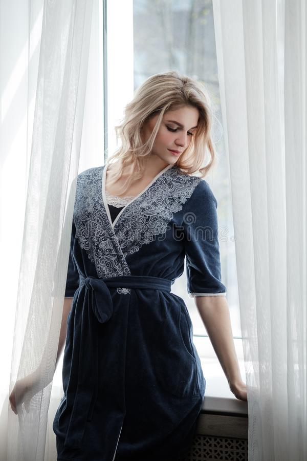 Beautiful young woman blonde in a blue robe by the window. Morning, sunshine, bedroom window royalty free stock images