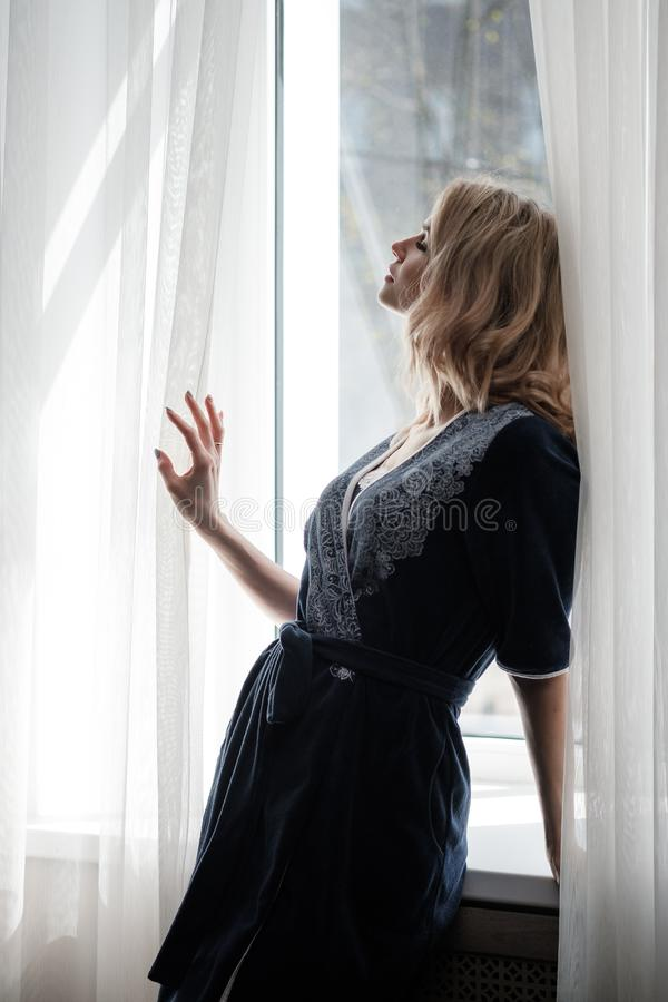 Beautiful young woman blonde in a blue robe by the window. Morning, sunshine, bedroom window stock image