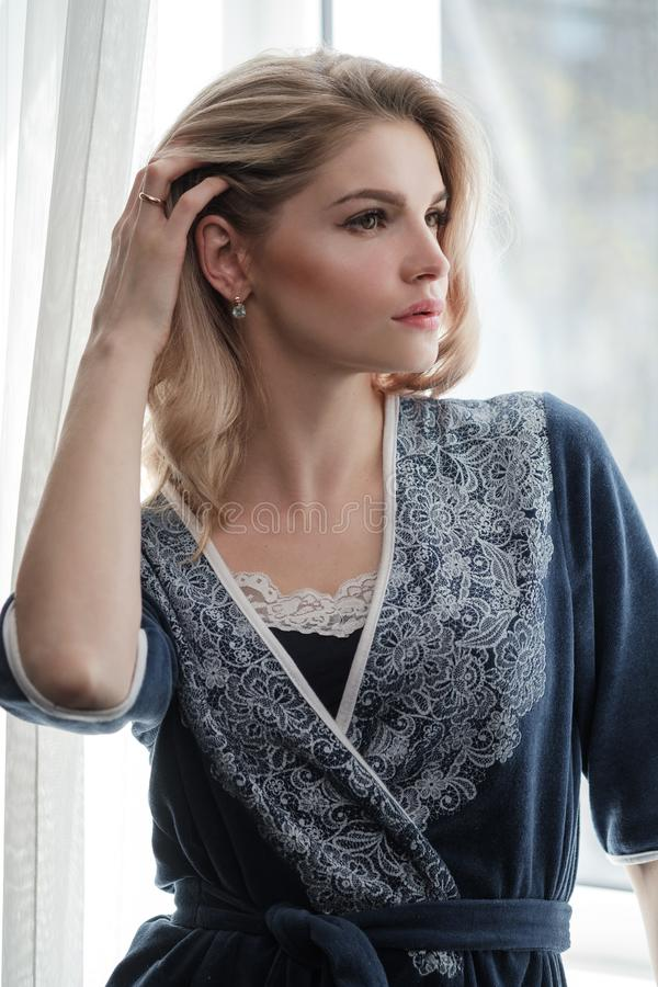 Beautiful young woman blonde in a blue robe by the window. Morning, sunshine, bedroom window stock photos