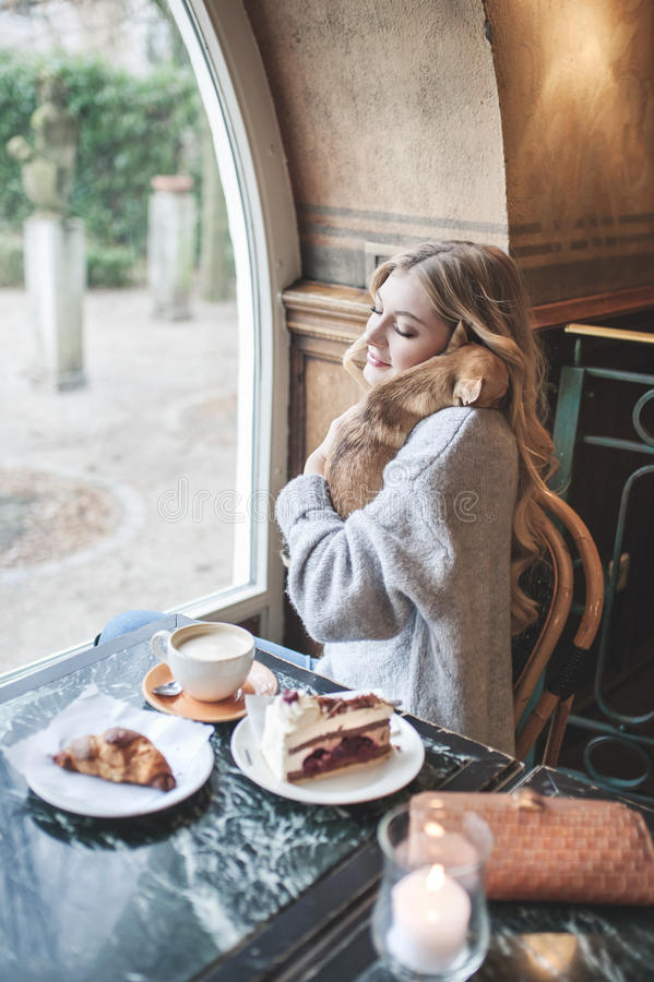 Beautiful young woman with blonde long hair spending time with h. Pretty young girl is spending time with her little dog while drinking a cup of coffee and royalty free stock photography